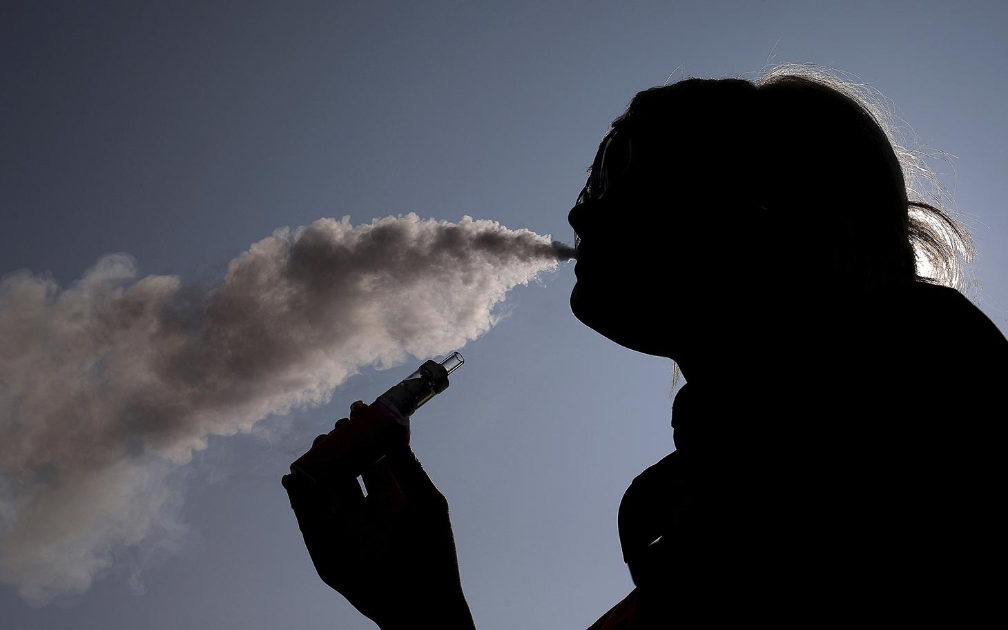 A woman exhales vapour from an e-cigarette outside the offices of British e-cigarette manufacturer Totally Wicked in Blackburn